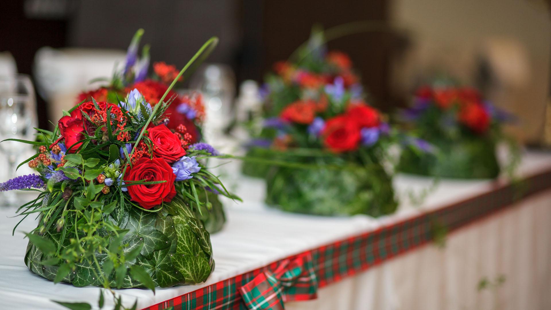 Цветна аранжировка с бръшлян за декорация на масата на младоженците