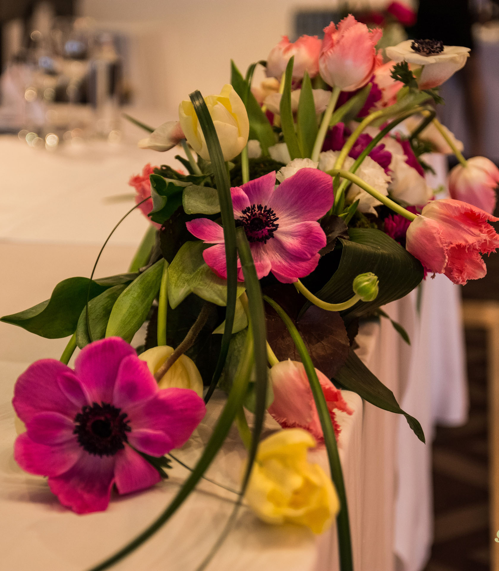 Цветна пролетна аранжировка с анемония и лале за масата на младоженците