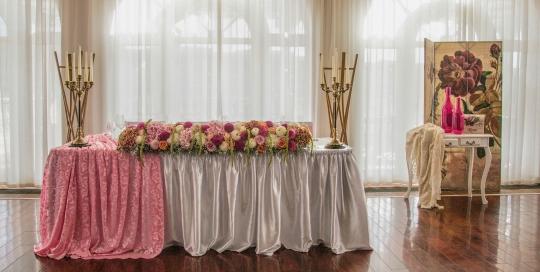 Сватбена декорация в нежно розово за масата на младоженците