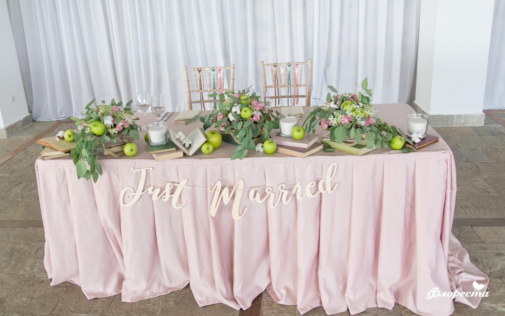 Декорация на масата на младоженците с цветни аранжировки от абълки, памук и мини рози