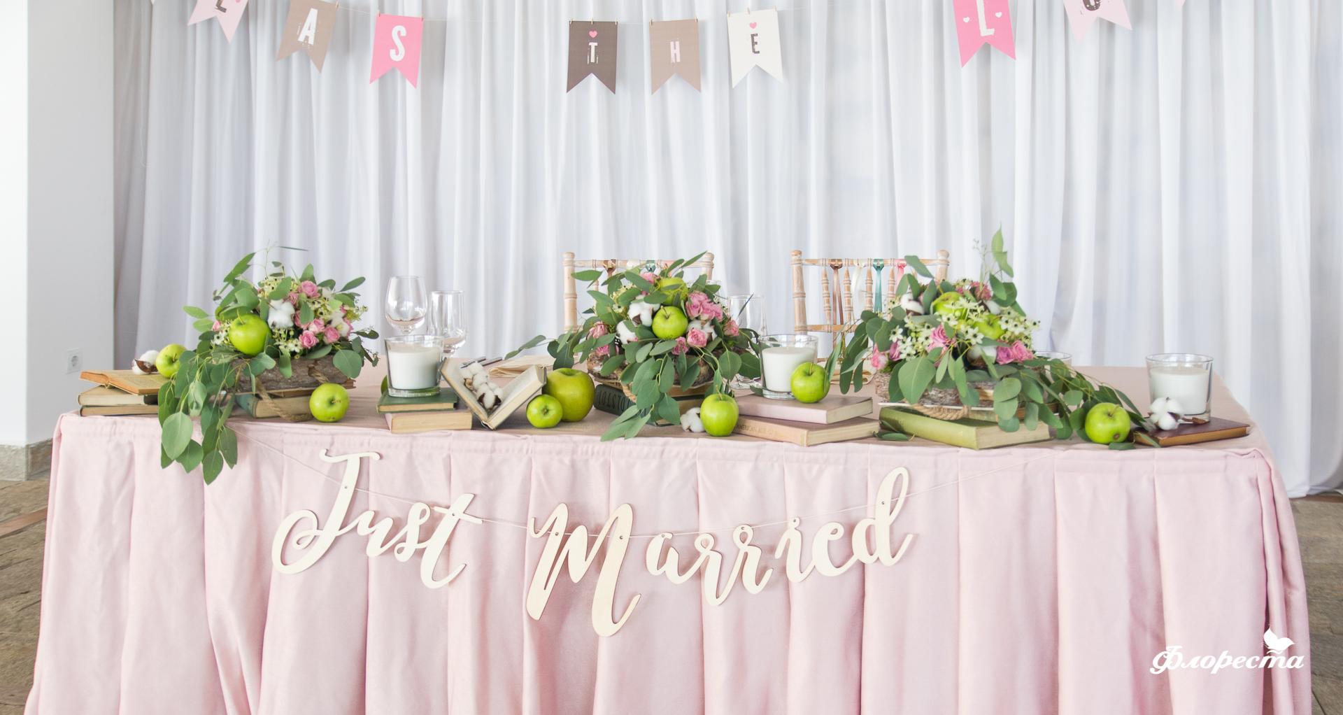 Декорация със зелени ябълки и памук в нежно розово на масата за младоженците